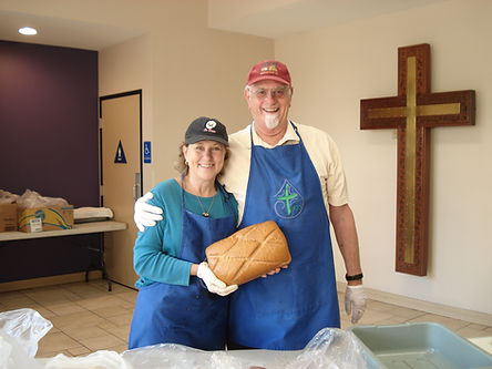 2 volunteers in blue aprons, caps, and gloves with one holding a bread