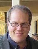 Bob Case, smiling, wearing glasses, shirt and jacket
