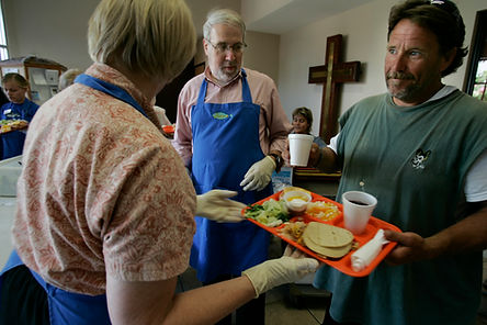 2 volunteers in blue aprons and man in green t shirt holding a tray of food
