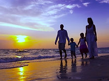 2 adults and 2 children walking on beach at sunset
