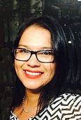Silvia Covarrubias, smiling, in black glasses, and black and white striped blouse