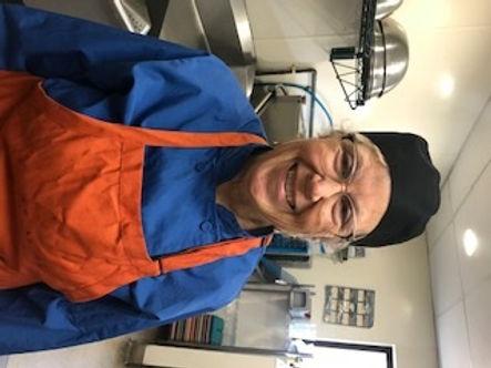 Cindy Quinonez, smiling, wearing orange apron, blue shirt, glasses and black cap