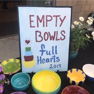 Colorful poster reads Empty Bowls Full Hearts 2019 next to many empty bowls