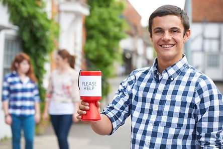 Young man in blue and white checked shirt holding a red and white cup with Please Help sign