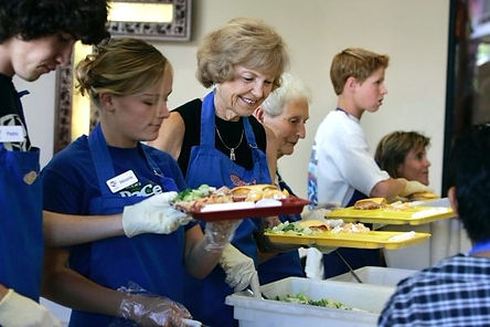 Volunteers of all ages helping serve a meal at TACO