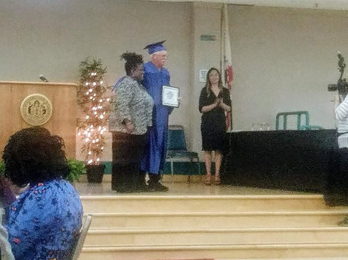 3 people on wooden stage, one man in blue graduation cap and gown holding diploma