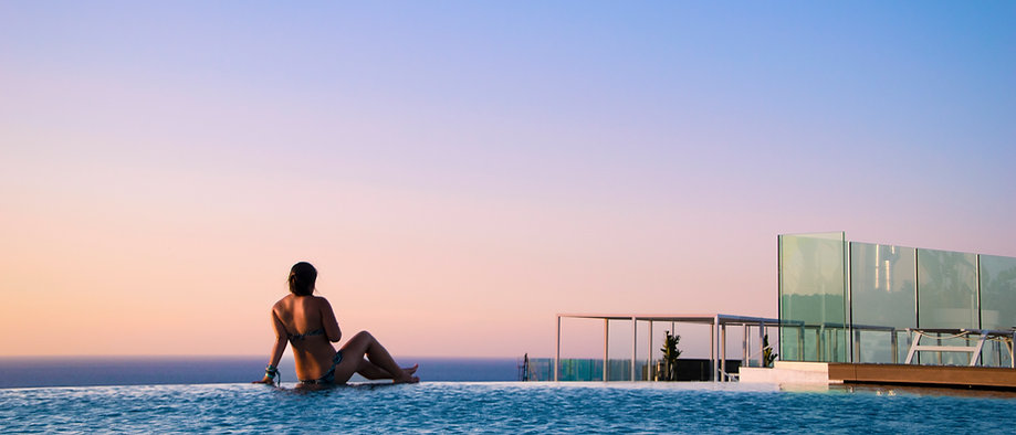 asian girl sitting in front of view in infinity pool