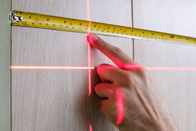 man measuring with tape with red laser l