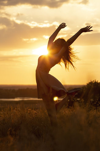 silhouette-of-a-beautiful-dreamy-girl-at-sunset-in-a-field,-a-young-woman-idance-with-happ