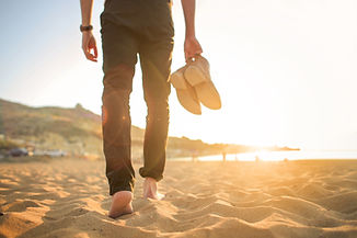 Man-walking-barefoot-in-the-beach-801824036_5760x3840.jpeg