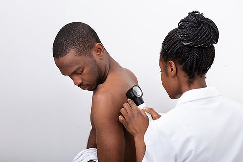 A dermatologist giving a patient a medical exam.