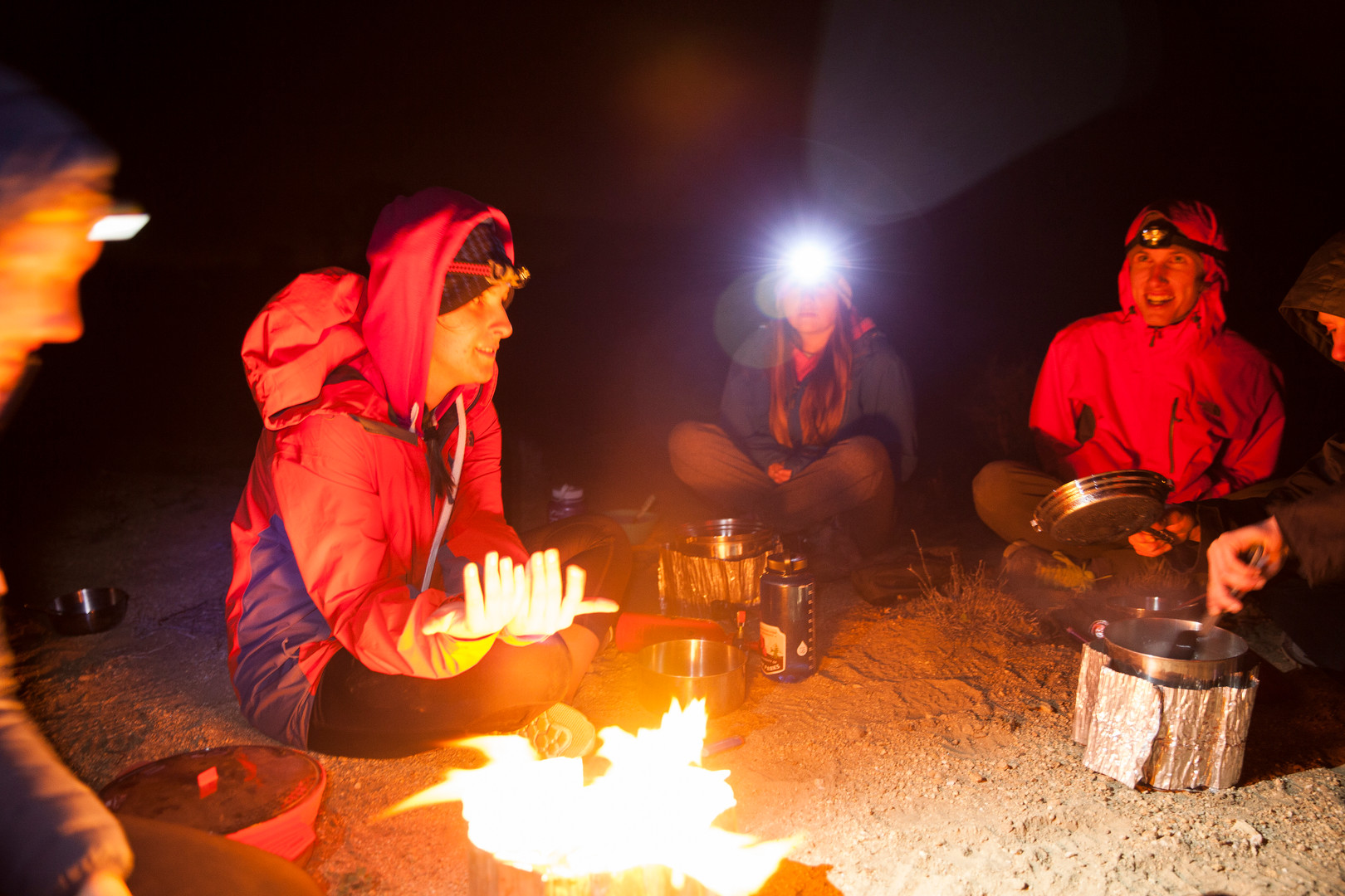 In a cold windy night, Rachel (visible at left) warms-up close by a stove, while Jessie (center with headlight on) and Rama (smiling at right) hang out with other elements of the group. During the Spring Break of the 2016 Spring Semester, a group of eight SUU backpackers traveled to Southern California to hike during 5 days, along the 37.3 miles of the California Riding and Hiking Trail in the desert of the Joshua Tree National Park. (photo-series 02/03) © March 2016