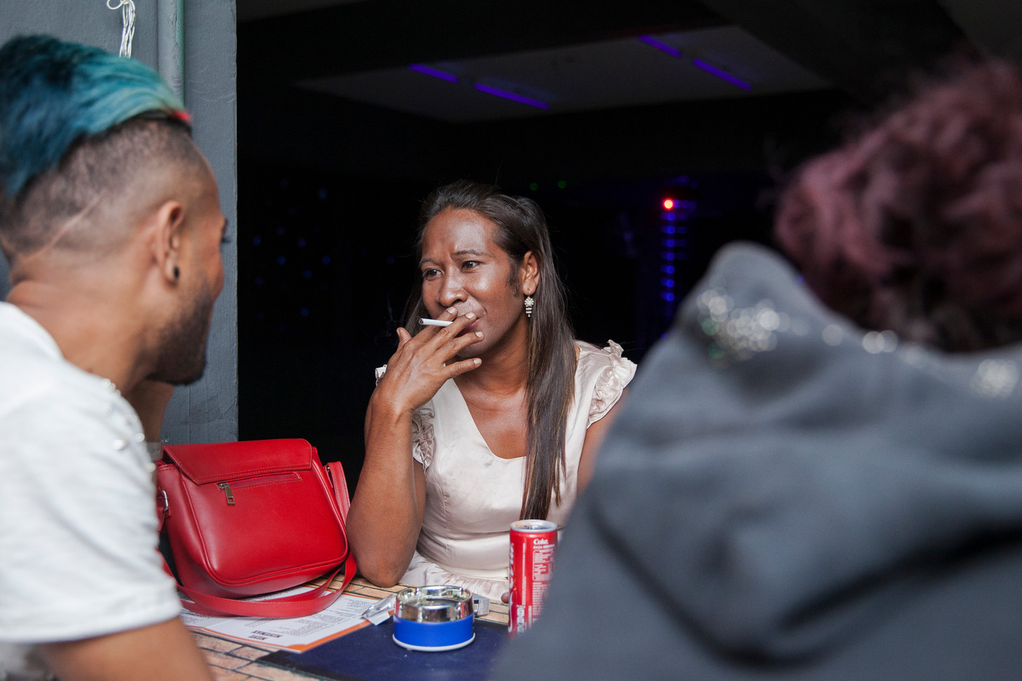 At the Colmera Shopping Center's nightclub, Romi Aty smokes a cigarette while having a conversation with a bartender. Growing up as transgender in a time where the LGBT movement wasn't established, it was challenging. In 2009, Aty became a sex worker, and even though she didn't do it for a long time, it was necessary to live an independent life.