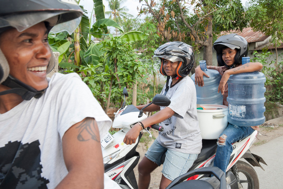 """Joker da Silva (right) and two of her closest friends from The Tomboy group, Mucho Leite (left) and Lula Sequeira (center), laugh right before they drive to Arco Iris, where they are going to leave materials used in a public event. Joker said, """"We were together because our parents couldn't accept us for who we were. They couldn't admit the reality. … As we stayed together, our lives were always on the street. We looked for some drinks; when there were parties, [and] if there was crowd, we would always be there. From Becora to Likintai, Likintai to Delta, we just walked. Every day just like this."""" However, nowadays it's different and while the movement is growing and many organizations like Arco Iris are being established, people like Joker and his friends find a safe place and guidance to become active members in East-Timor."""