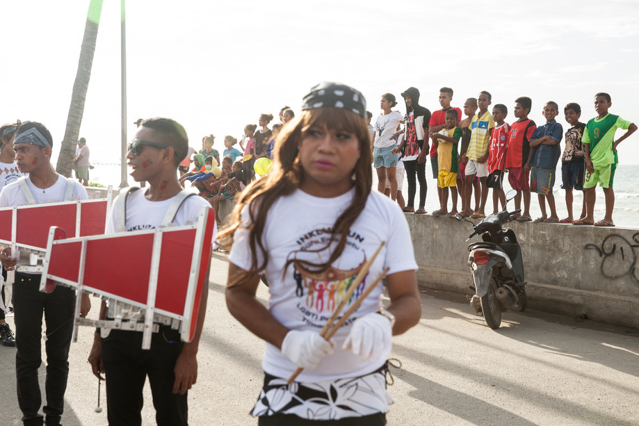 """Young people watch the 2018 Gay Pride parade from the side of the road, while members of the transgender marching band wait to start playing music. Hundreds of people came out on the streets of Dili to support the cause of the LGBT community. The main person behind the pride, Natalino Guterres, said, """"People see it in different ways, some people see it as a protest, some people see it as a celebration of our existence. … we exist, and we are part of this country and a lot of us are also contributing to the development of this country."""""""