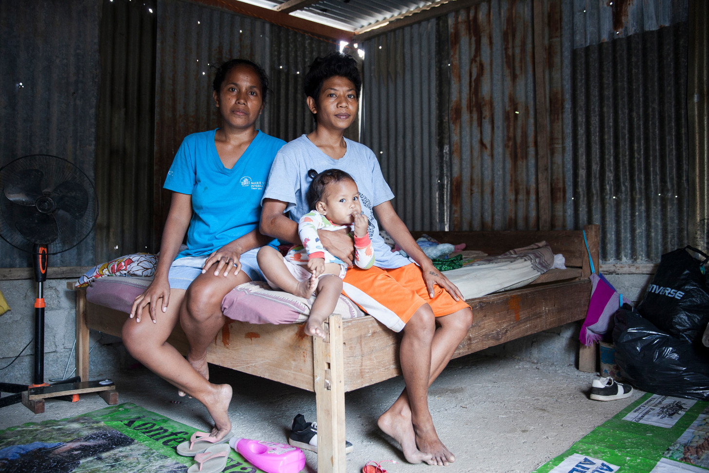 """Zelia da Costa (left), Joker da Silva and little Neurgia pose for a portrait in their house, located in the neighborhood of Has-Laram, Dili, capital of East-Timor. Living together as a same-sex couple in East-Timor has its challenges. Even though Joker wants to be treated as a man, many people see him as a woman. Da Costa and Joker face discrimination, stigma and violence for being a non-traditional couple. Many Timorese people describe them as monsters and a curse of God. """"The society comes up with norms, like: A man has to wear man's clothes, and work like a man. That is why there's discrimination against us,"""" Joker said. """"When I go to the church, many people keep staring at me, like I am a criminal. If I wear these kinds of clothes [like shorts and shirts], why should I go?"""" Da Costa is Neurgia's biological mother from a man she never loved. Da Costa fall in love with Joker, despite the pressures coming from her own family. """"I felt so much secured with her, there was peace and joy, I just wanted to be with her,"""" Da Costa said."""