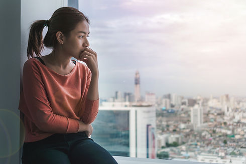 PTSD Mental health concept, Young depressed asian woman sitting near window with low light