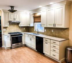 White kitchen with stainless steel stove and hood.