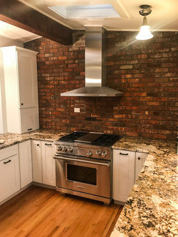 Brick wall with stainless steel hood in ktichen.
