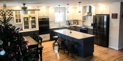 Kitchen with large island, dining table and industrial style light pendants.