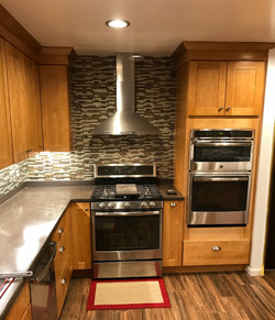 Oak kitchen with glass backsplash and stainless steel hood.