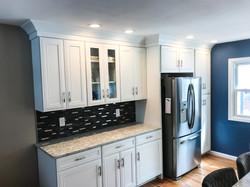 White kitchen, dark grey backsplash and stainless steel refrigerator
