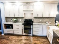 White kitchen with granite pensinsula.