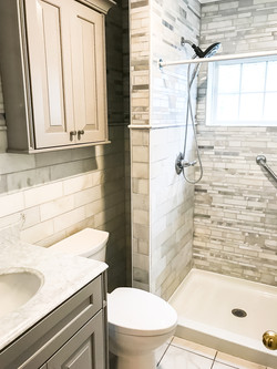 grey tile vanity, mirror, toilet and storage