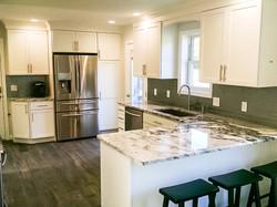 White kitchen with granite peninsula and stools.