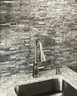 Brushed nickel kitchen faucet with dark grey tile backsplash.
