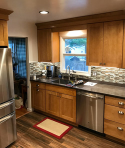Oak cabinets with glass tile backsplash and grey countertop.