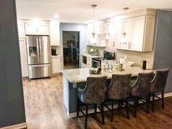 White kitchen with granite peninsula.