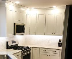 White shaker cabinets with white subway tile backsplash.