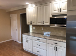 White kitchen with microwave and beige tile backsplash