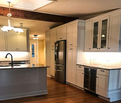White shaker kitchen cabinets with wine fridge.