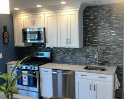 White kitche, stainless steel stove and dark grey tile backsplash.