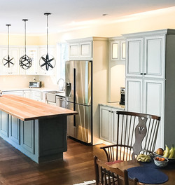 grey kitchen with round pendants over butch block island