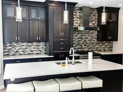 Espresso kitchen, large island with glass tile backsplash.