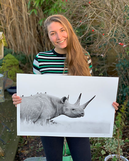 Lara holding a print of the black rhino Waiwai on Lewa Wildlife Conservancy in Kenya