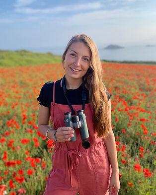Lara in the poppy fields of West Pentire in Newquay Cornwall with her Swarovski binoculars