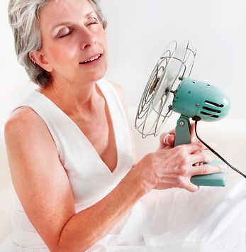 A woman having a hot flash using a fan t
