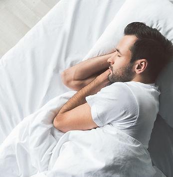 Cute young man sleeping on bed.jpg