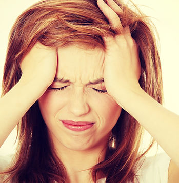 Teen woman with headache holding her han