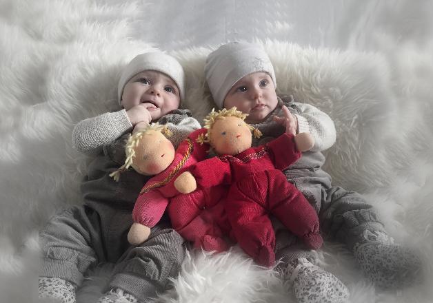 Zwillingsbabies mit Zwillingspuppen
