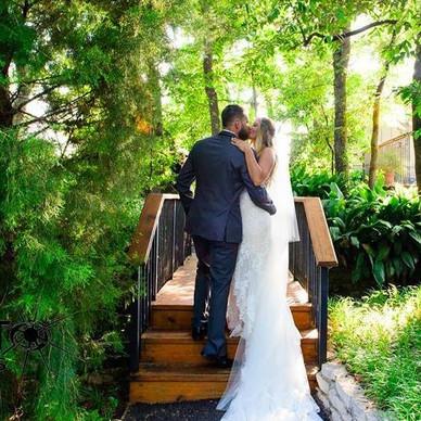 Bride and Groom on outdoor bridge in The Gardens
