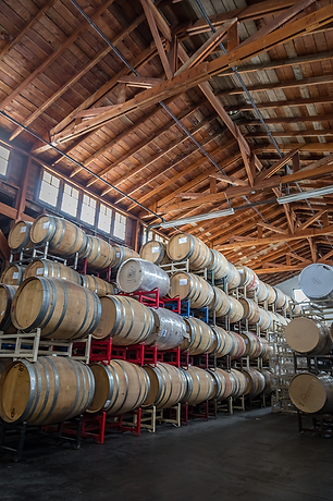 wine barrels stacked in the Pallet Wine Company winery in Medford, Southern Oregon..png