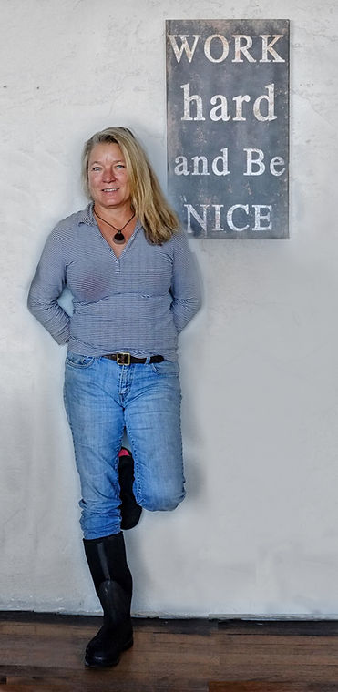 """picture of Oregon winemaker Linda Donovan against a wall and a sigh that reads """"work hard and be nice"""""""