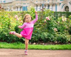 little girl dancing in the park like bal