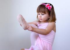 Little ballerina dancer putting on her s