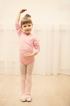Little cute girl in pink leotard making